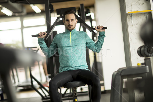 Young man doing exercise for triceps in the gym on mashine Stock photo © boggy