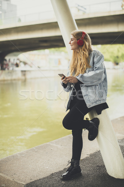 Young pretty woman posing in the street on headphones, listening Stock photo © boggy