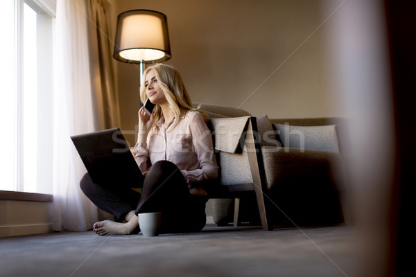 Young woman sitting on the floor and working on lap top Stock photo © boggy
