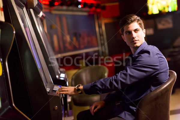 Young man with slot machine in the casino Stock photo © boggy