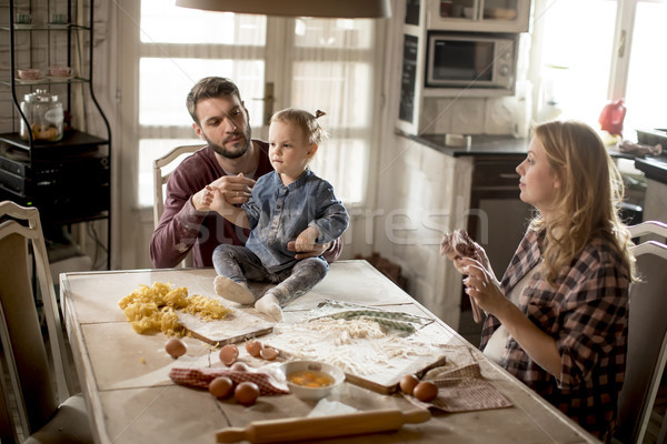 Happy family making pasta in the kitchen at home Stock photo © boggy