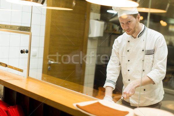 Young chef preparing food in the kitchen Stock photo © boggy