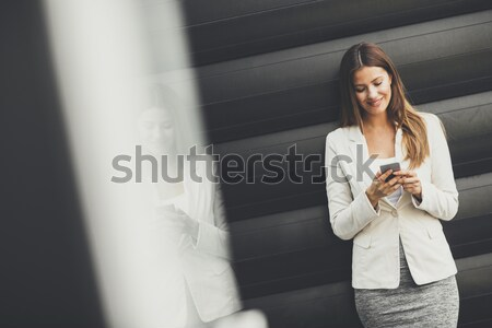 Businesswoman using mobile phone Stock photo © boggy