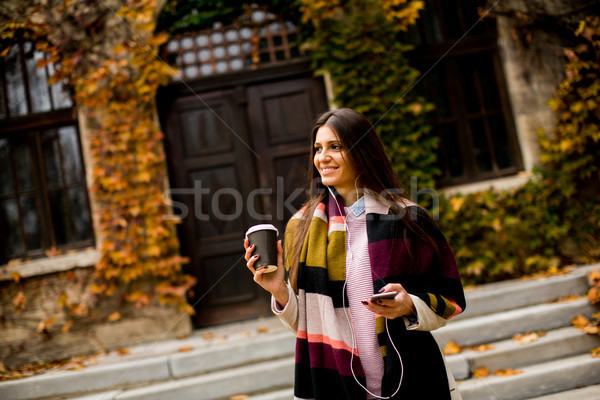 Young woman standing outside, drinking coffee to go and holding  Stock photo © boggy