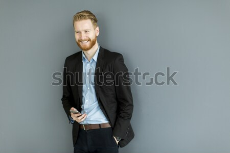 Redhair man using mobile phone standing by the wall Stock photo © boggy