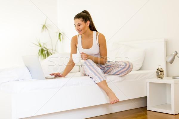 Mulher potável café casa cama Foto stock © boggy