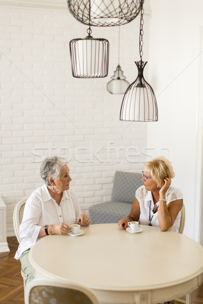Two older women drinking coffe at home and talking Stock photo © boggy