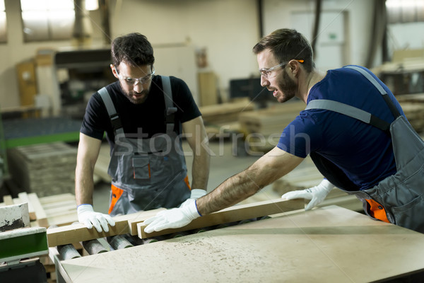 Young men working in lumber workshop Stock photo © boggy