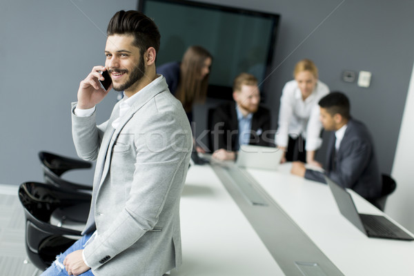 Beard businessman using mobile phone in office while other busin Stock photo © boggy