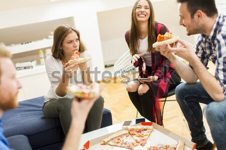 Small group of young friends eating pizza in the room Stock photo © boggy