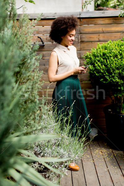 Curly hair young woman with a phone in his hand in the courtyard Stock photo © boggy