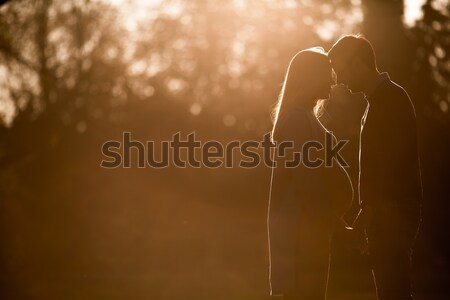 Pregnant woman and man posing at autumn park Stock photo © boggy