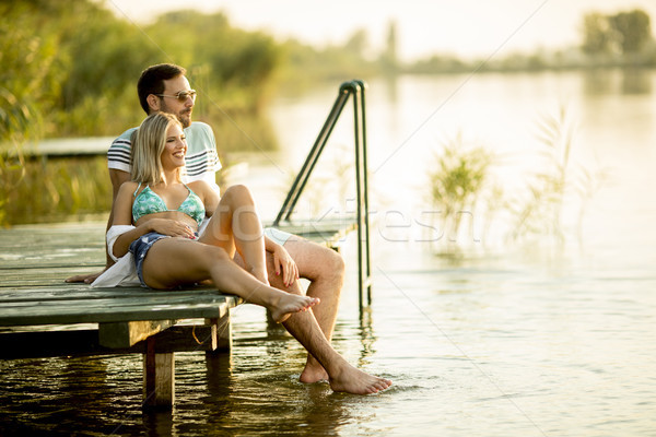 Romantic couple sitting on the wooden pier on the lake Stock photo © boggy