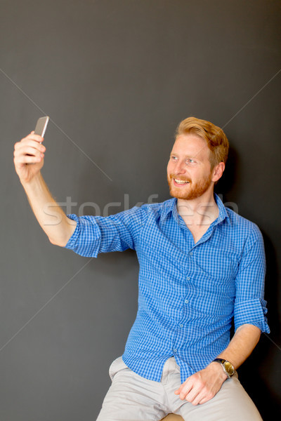 Ginger man taking selfie isolated on black Stock photo © boggy