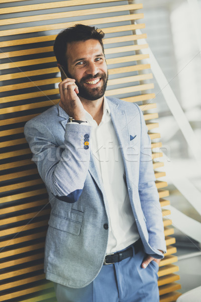 Handsome young businessman using phone in office Stock photo © boggy