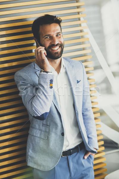 Guapo jóvenes empresario teléfono oficina vista Foto stock © boggy