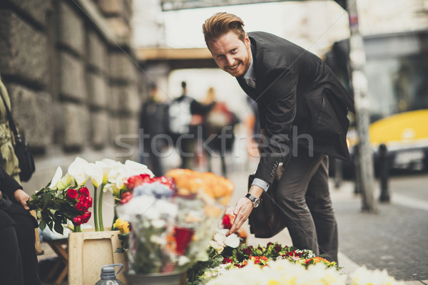 Young man buys flowers from street vendors Stock photo © boggy