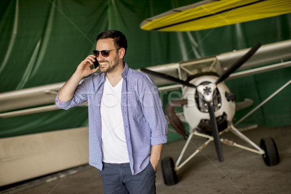 Young man using mobile phone in the airplane hangar Stock photo © boggy