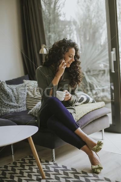 вьющиеся волосы мобильного телефона кружка сидят Сток-фото © boggy