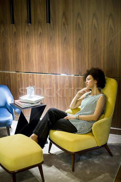 Mulher jovem cabelos cacheados sessão amarelo cadeira Foto stock © boggy