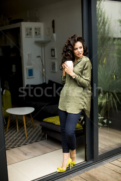 Modern woman standing next to a glass door and drinking coffee Stock photo © boggy