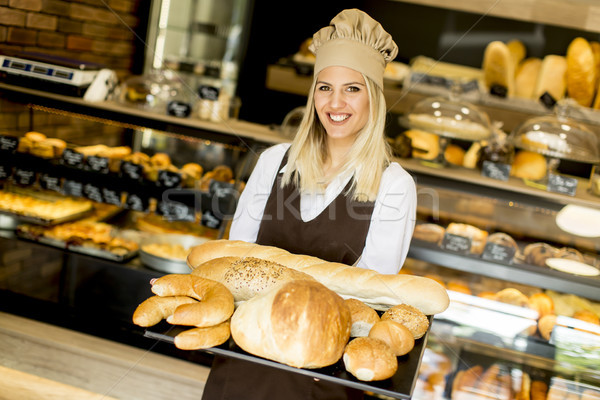Female bakery posing with various types of pastries and breads i Stock photo © boggy