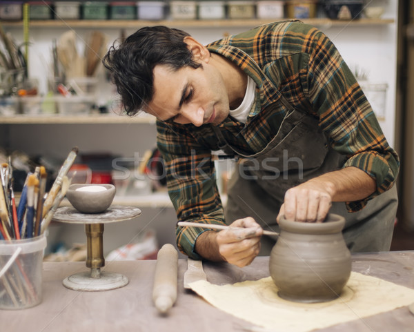 Young man making pottery in workshop Stock photo © boggy