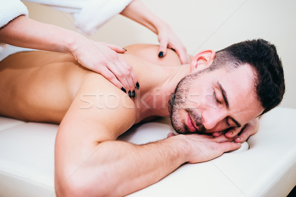 Man having back massage from masseur in spa Stock photo © boggy