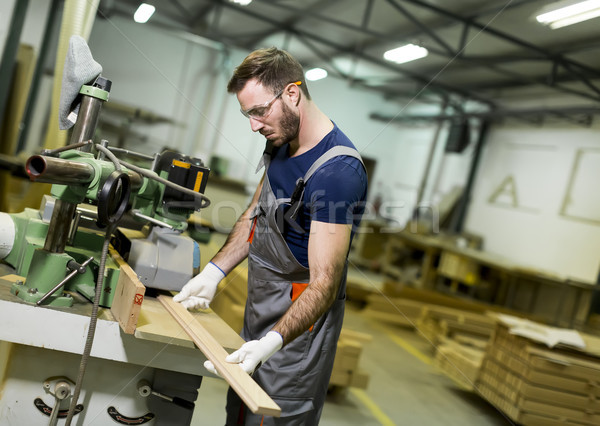 Handsome young man working in the furniture factory Stock photo © boggy