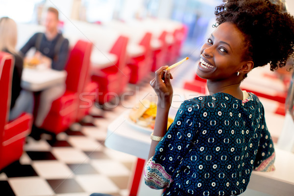Young african american woman eating in the diner Stock photo © boggy