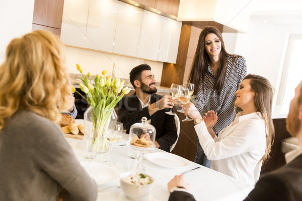 Friends having a meal at dining table and toast with  white wine Stock photo © boggy