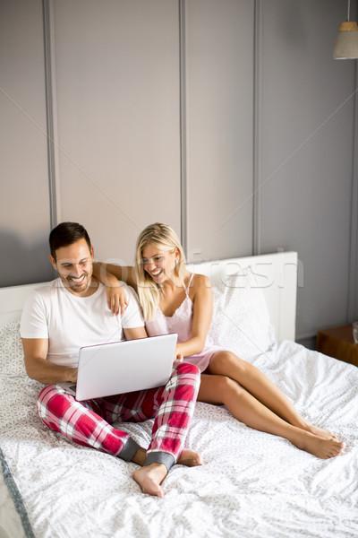 íntimo amantes usando la computadora portátil sesión cama dormitorio Foto stock © boggy
