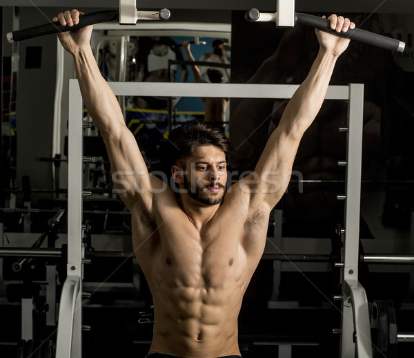 Young male adults doing pull ups in the gym Stock photo © boggy