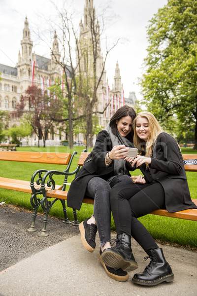 Women with mobile phone on bench in public park Stock photo © boggy