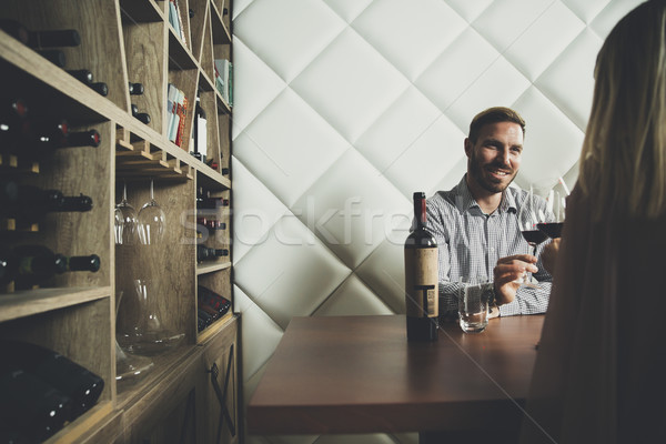Handsome young couple on the date sitting by table in wine bar Stock photo © boggy