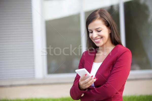 Jeunes femme d'affaires rouge blazer téléphone portable extérieur Photo stock © boggy