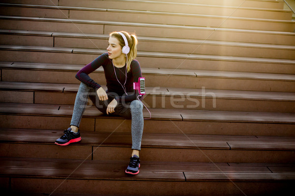 Stock photo: Pretty young woman takes a break after running