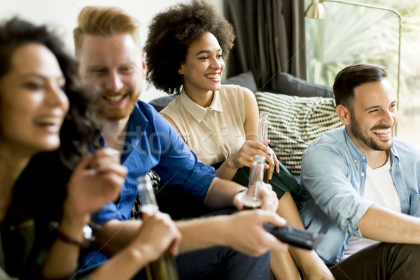 Group of friends watching TV, drinking cider and having fun Stock photo © boggy