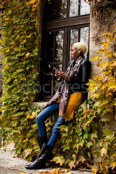 Stock photo: Pretty young black woman with mobile phone in the autumn park