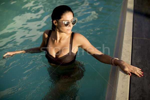 Pretty young woman relaxcing on the poolside Stock photo © boggy