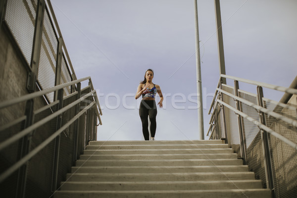 Young woman running alone down the stairs Stock photo © boggy