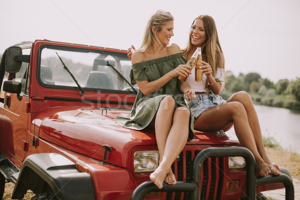 Attractive young women on a convertible car by river Stock photo © boggy