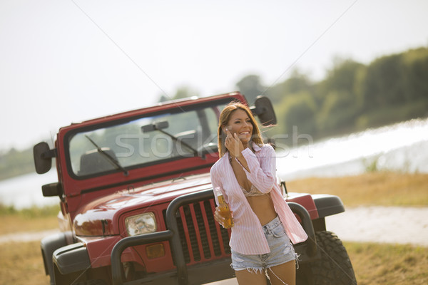 Young woman standing in front of red cabrio car Stock photo © boggy
