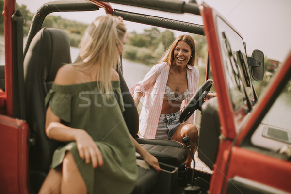 Attractive young women in a convertible car Stock photo © boggy