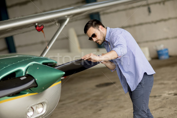 Handsome young pilot checking his ultralight airplane before fli Stock photo © boggy