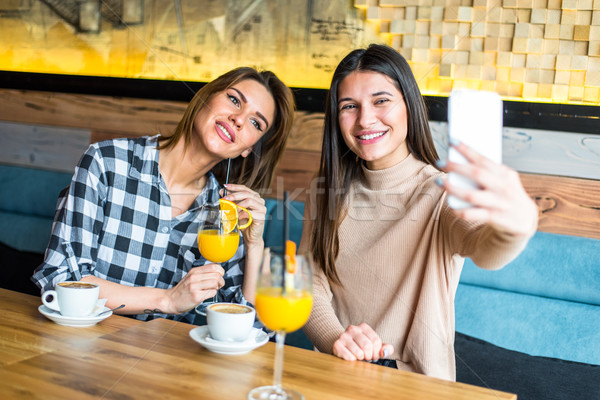 Two pretty young women taking selfie in the cafe Stock photo © boggy