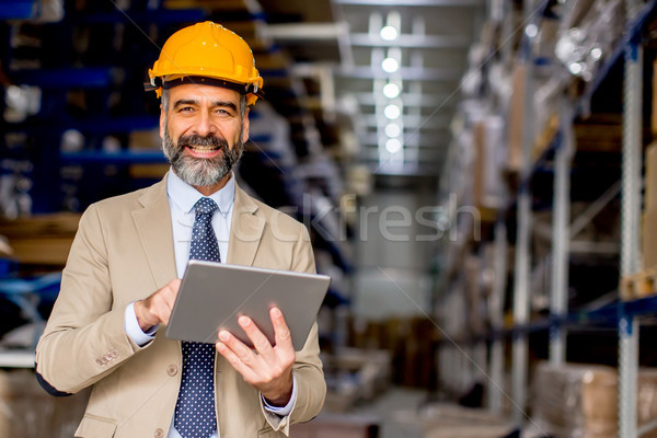Mature engineer in the warehouse with digital tablet Stock photo © boggy
