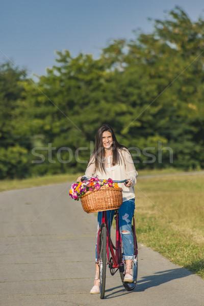 Stok fotoğraf: Genç · gülümseyen · kadın · bisiklet · sepet · tok · çiçek