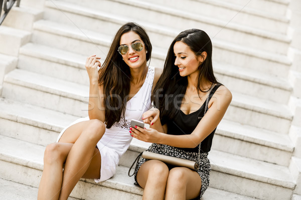 Two women sitting on the stairs outside and using mobile phone Stock photo © boggy