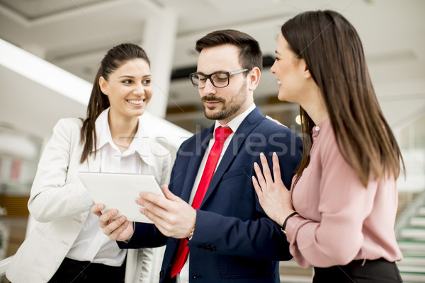 Smiling business team working with tablet pcs in office Stock photo © boggy